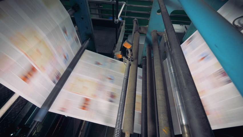 Conveyor with numerous freshly printed newspapers. 4K. Royalty-Free Stock Footage #1008826235