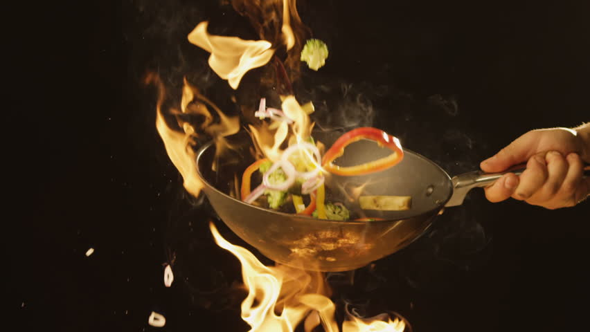 Chef Frying vegetables on fire throwing them in a frying pan #1008828392