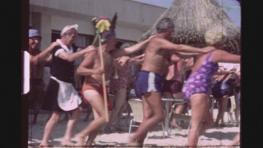SPAIN, MALLORCA, JULY 1983. A Group Of Female And Male Caucasian Tourists Dancing Happily In A Conga Line Circle In Bathing Suits At A Beach Bar.