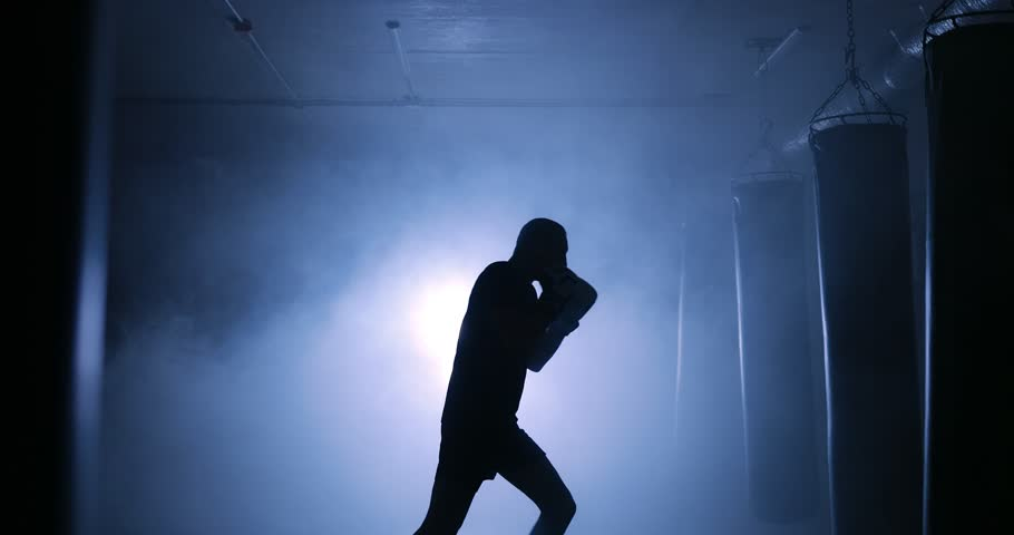 Strong male boxer training in a dark smoky room. Silhouette on a dark background | Shutterstock HD Video #1008842063
