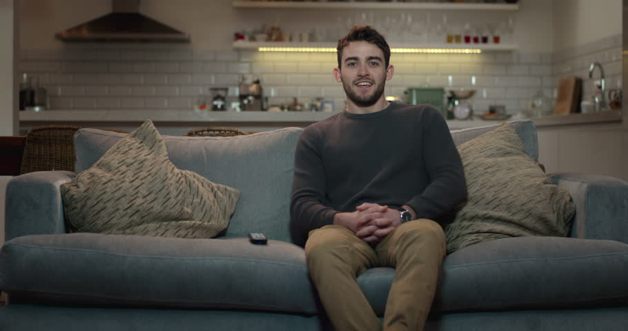Young, attractive man sits down on a couch and turns on the television using a remote control. #1008851162