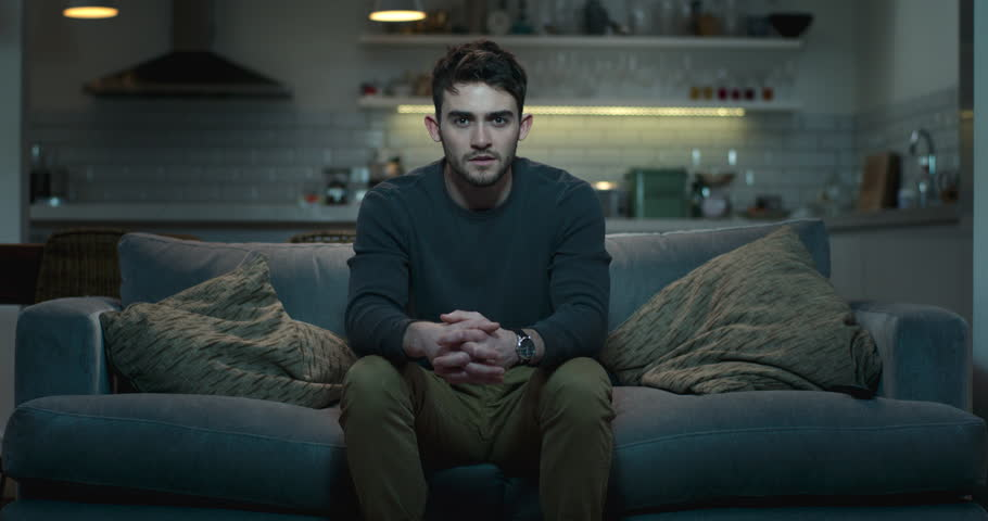 Young man sitting on the edge of a couch watching a scary movie. | Shutterstock HD Video #1008851177