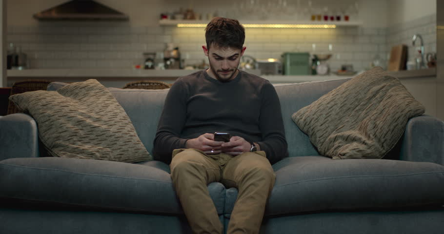 Young, good-looking man using his  smartphone while sitting in front of the tv. | Shutterstock HD Video #1008851243