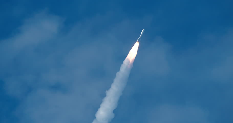 Space Rocket flying against deep blue sky with bright flames and dense exhaust smoke form the solid rocket boosters. 4K at 120 fps slow motion.