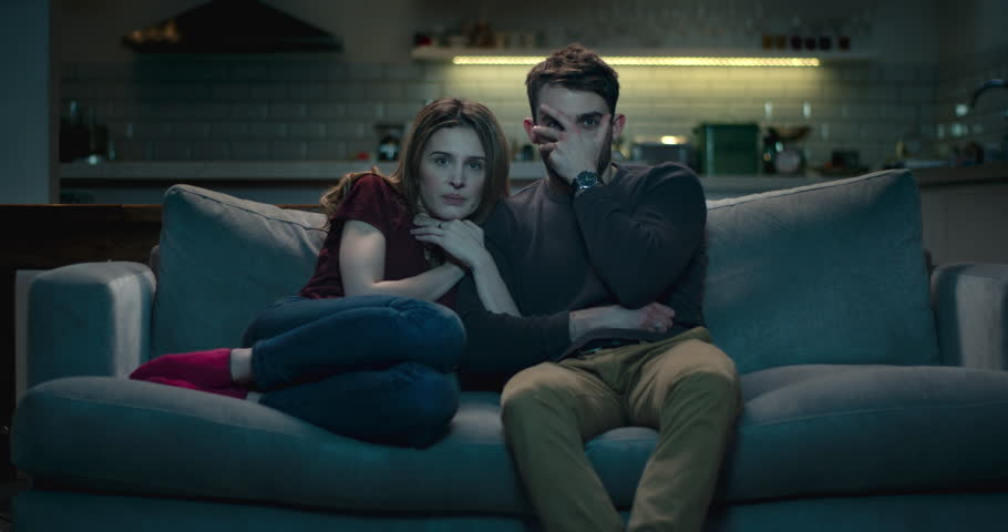 Frightened couple on a sofa late at night watching a scary horror film.