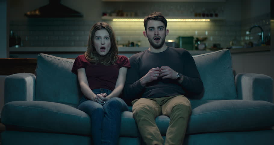 Couple on a sofa at home react to a shocking moment on screen.
