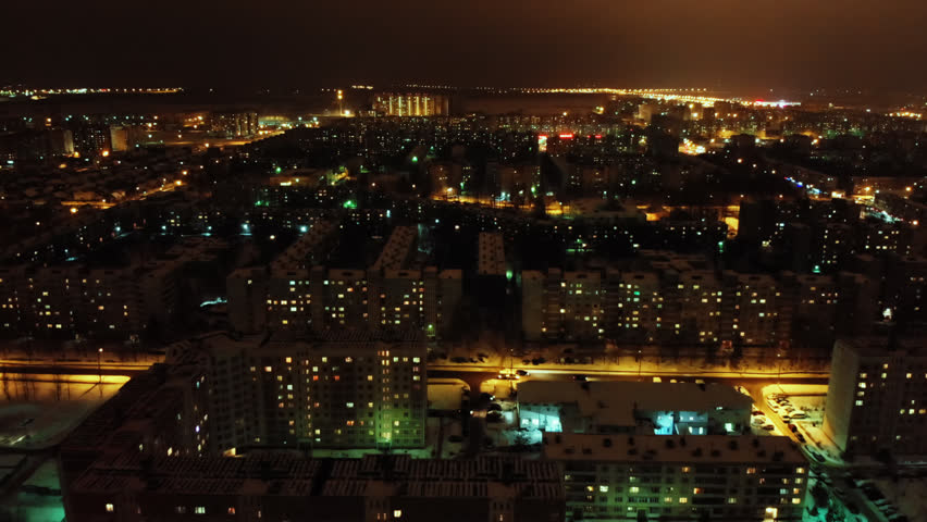 Aerial flight shot above russian night city lights. Cold evening winter town with old soviet buildings. Downtown cityscape