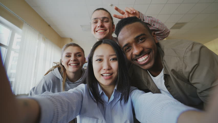 POV of asian girl holding smartphone taking selfie photos with cheerful multi-ethnic classmates and have fun at university library. Woman pointing touchsreen and watching pictures