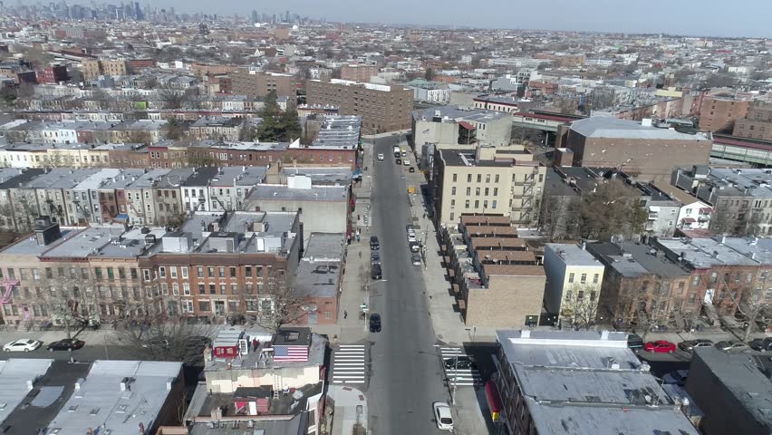 Drone shot, high and expanded view of Brooklyn, with the Newyork city view in the background, drone flying capturing streets, cars, daylight sky, birds and American flag