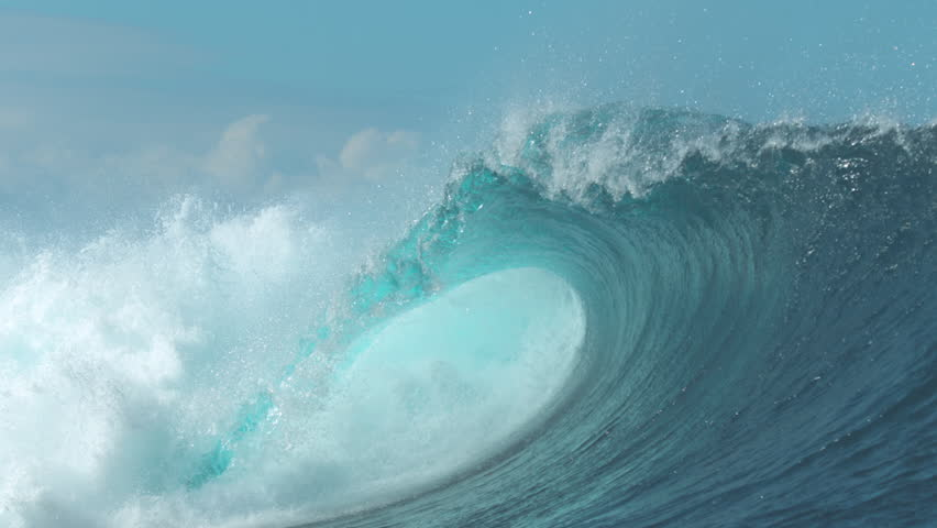SLOW MOTION, CLOSE UP: Powerful Cloudbreak wave violently swirls in cool sunny weather. Majestic emerald ocean wave crashes on perfect summer day. Giant tube wave breaks violently and glimmers in sun.