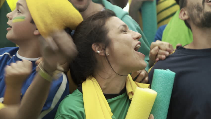 Brazilian soccer fans watching match at stadium and cheering excitedly