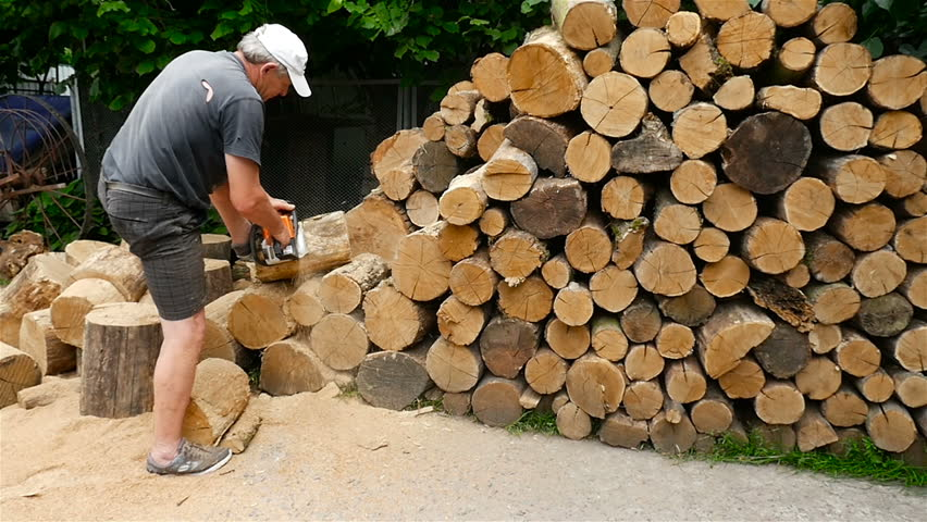 A man is sawing wood with a chainsaw. Slow motion | Shutterstock HD Video #1008906470