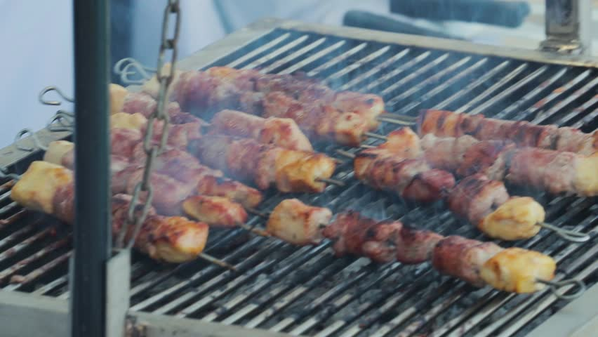 Chicken kebabs cooking on a barbecue.   Shutterstock HD Video #1008913223