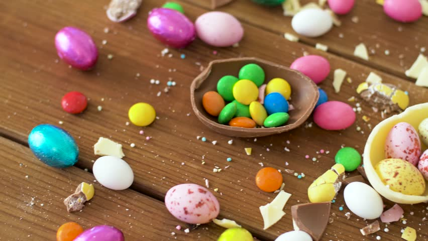 Easter, junk-food, confectionery and unhealthy eating concept - chocolate eggs and drop candies on table | Shutterstock HD Video #1008922262