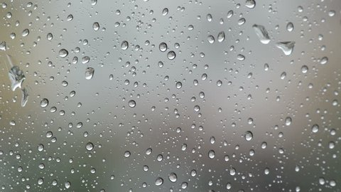 Drops of rain in the glass of a window while it's raining outside