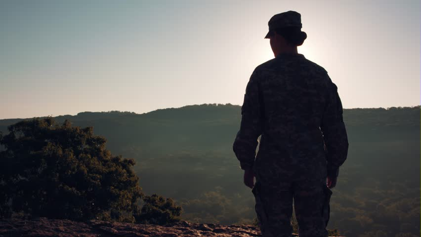 Soldier looking out over mountains at sunrise | Shutterstock HD Video #1008923447