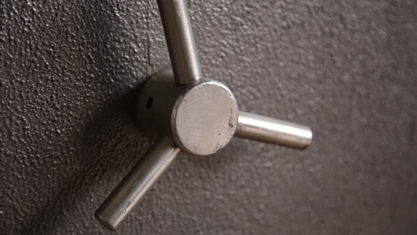 Hand opening and locking a bank safe with handle