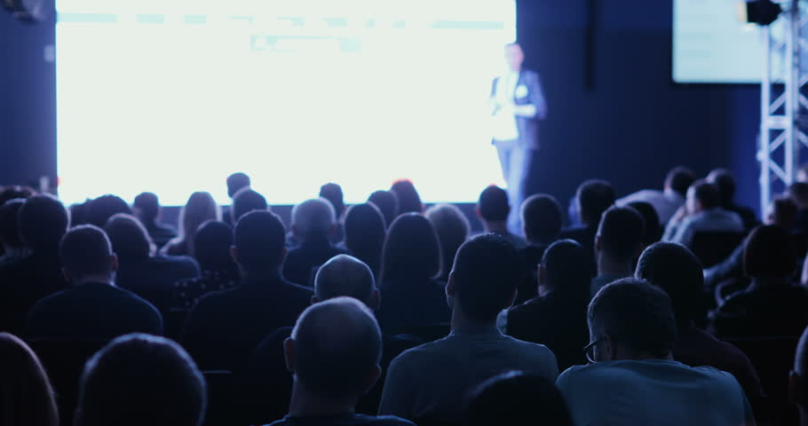 lecturer tells and shows presentation on projective screen to packed house of listeners #1008956918