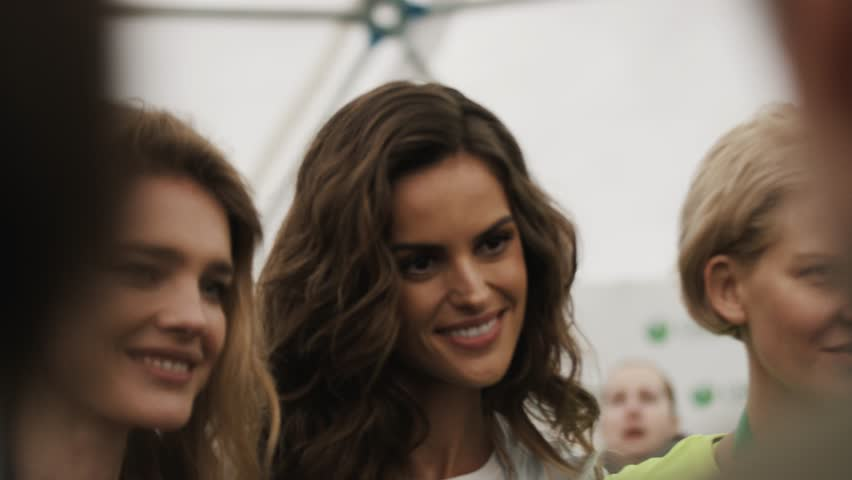 MOSCOW, RUSSIA - MAY 28, 2017: Russian model Natalia Vodianova posing with Izabel Goulart at sportive event in white tent, slow motion #1008961379