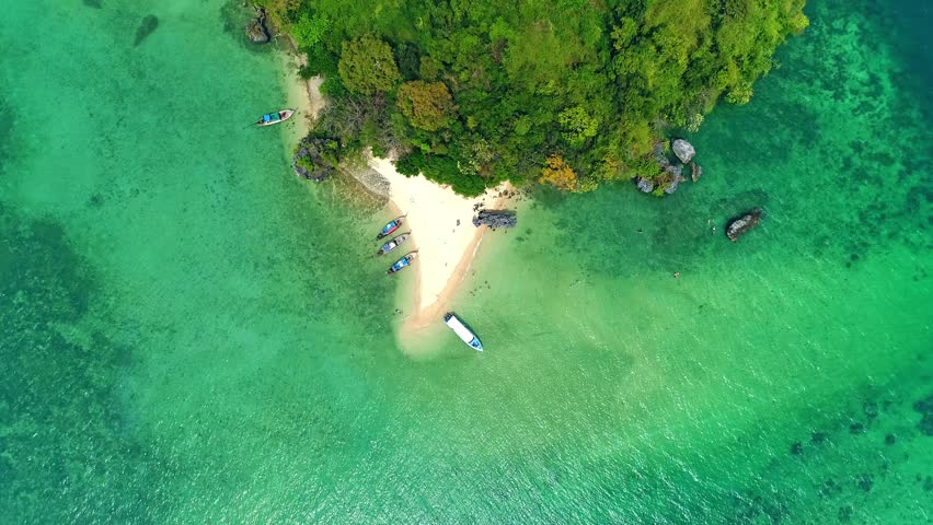 AERIAL. Top view of tropical islands, boats and cliffs
