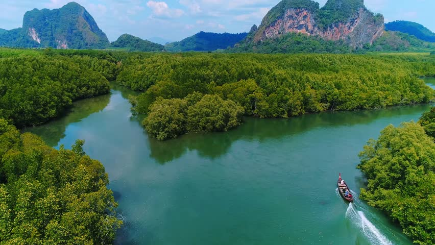 AERIAL. Top view of traditional thai boat at Krabi, Thailand. Mountains on background