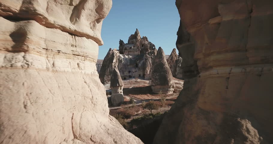 Advancing aerial drone footage flying between fairy chimneys revealing many cave houses carved into hoodoo mountain above Rose Valley and Cappadocia nature landscape in Goreme, Turkey. 4k at 23.97fps