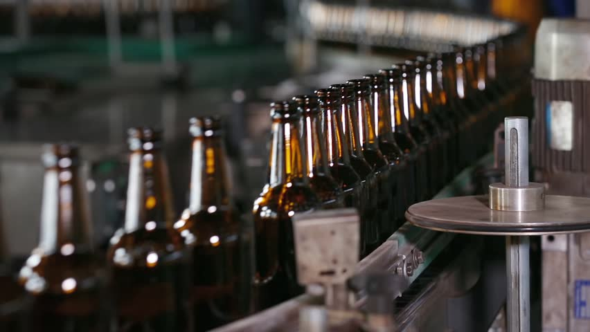 Technological line for bottling of beer in brewery. Empty brown bottles in a line in factory. Bottles Moving on Conveyor Belt at Glass Bottle Factory. Clean beer bottles are moving along the conveyor.
