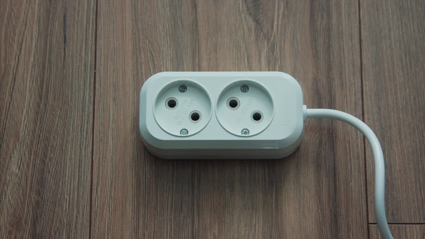 Male hand plugging black power plug into white multiple socket indoors in slow motion. Electricity concept.