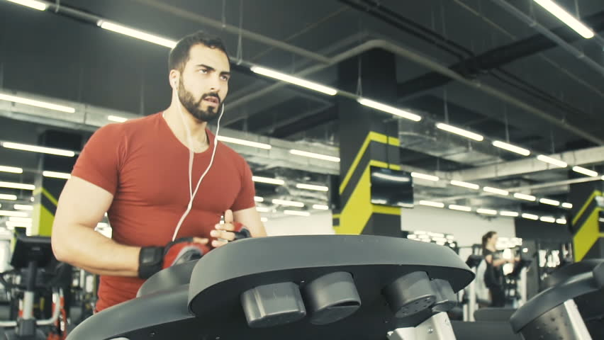 Muscular handsome man running in the gym, cardio exercise concept #1008985538