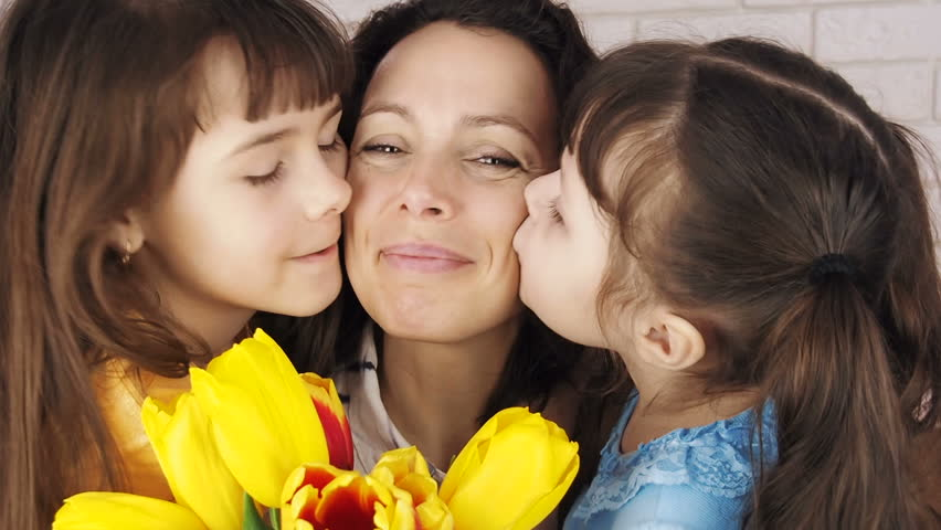Mothers Day. Daughters kiss mother.