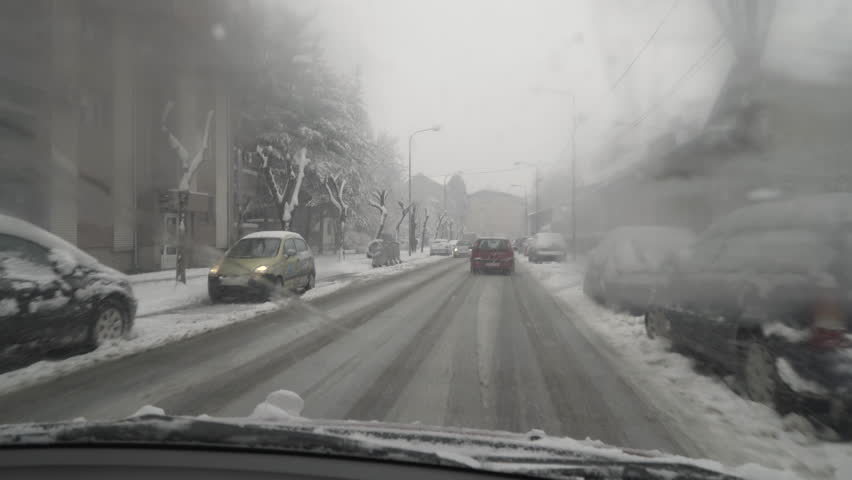 Snow falling on city street,POV inside car in drive through wet windshield during wipers cleaning snowflakes and drops,parked vehicles under snow,automobile passing,people walking on sidewalk.close up