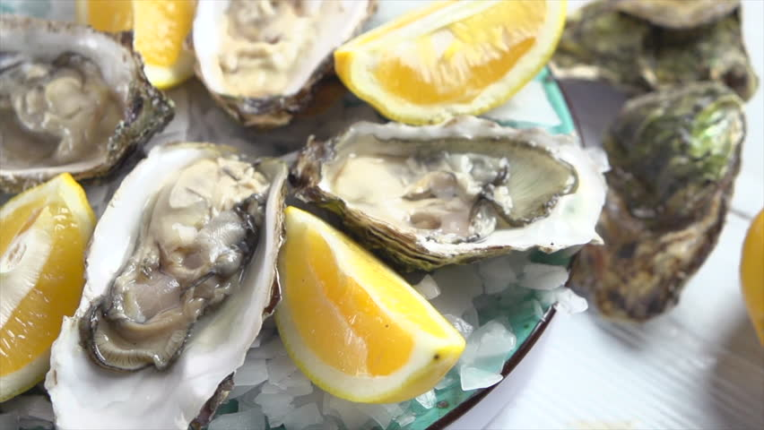 Oysters on ice with lemon closeup. Fresh Oyster on half shell on big plate in restaurant. Served table. 4K UHD video slow motion | Shutterstock HD Video #1008998117