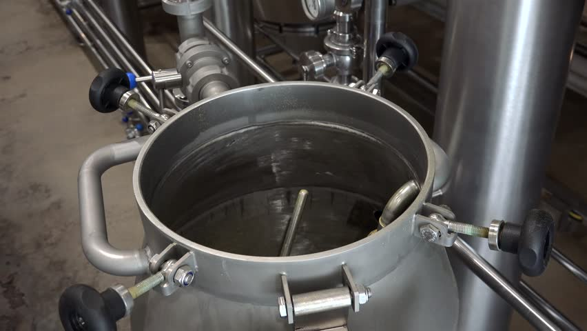 Modern Craft Brewery. Hop dosing in the Hop Extractor vessel (IPA production).
