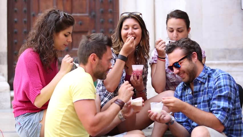 Tourists or friends eating ice cream slush, talking and looking each other. Five persons having fun together on a hot summer day in Pisa, Italy. Women and men sitting on concrete steps and relaxing. #1009001384