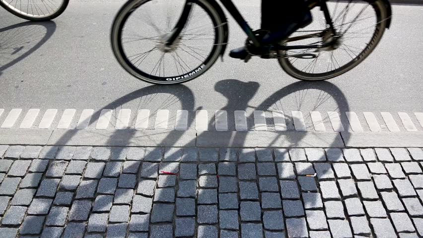 People cycling in Copenhagen, focus on bicycle shadows. Side view of a bicycle lane in the Danish capital, with many persons commuting by bike.   Shutterstock HD Video #1009001606