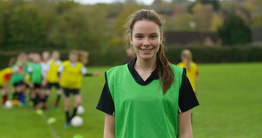 4K Portrait smiling British girl at soccer training, with team mates in the background. Slow motion. Royalty-Free Stock Footage #1009004573