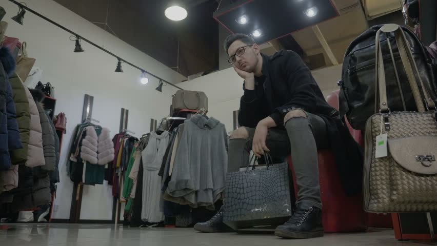 Bored fashionable man holding shopping bags and waiting for his girlfriend to try on clothes in a store at the mall
