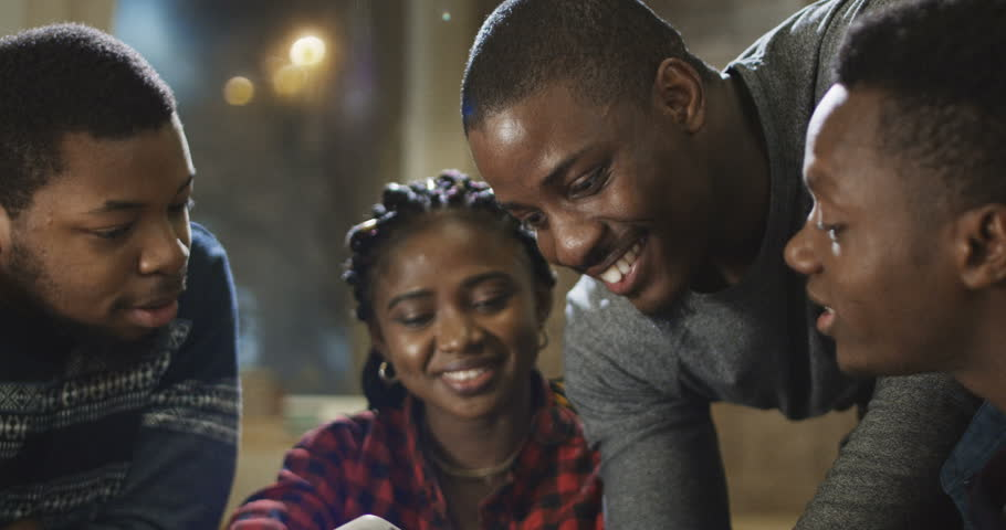 Group of laughing African-American men and girl watching phone and laughing while chilling in cafe. | Shutterstock HD Video #1009020812