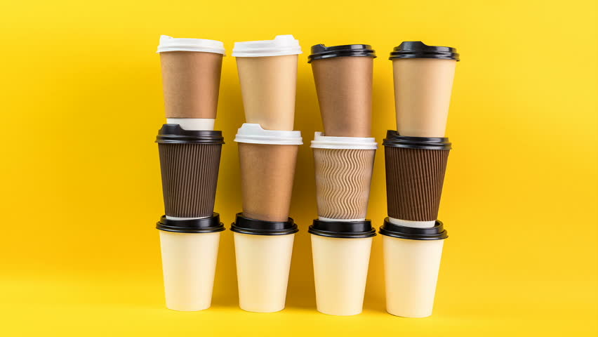 A lot of disposable cups for coffee and tea change places. Nice catering for a coffee shop. Video footage stop motion timelapse. Bright yellow background. Coffee take away ( to go ) #1009026110