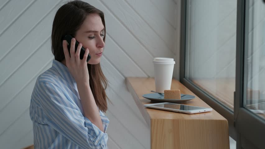 Beautiful blue-eyed woman talking on a mobile phone during lunch | Shutterstock HD Video #1009048862