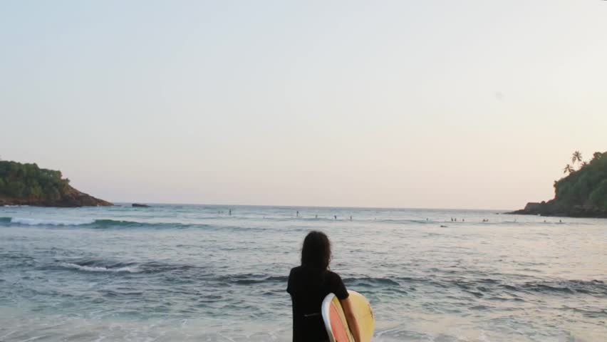 girl with surfboard by the ocean.