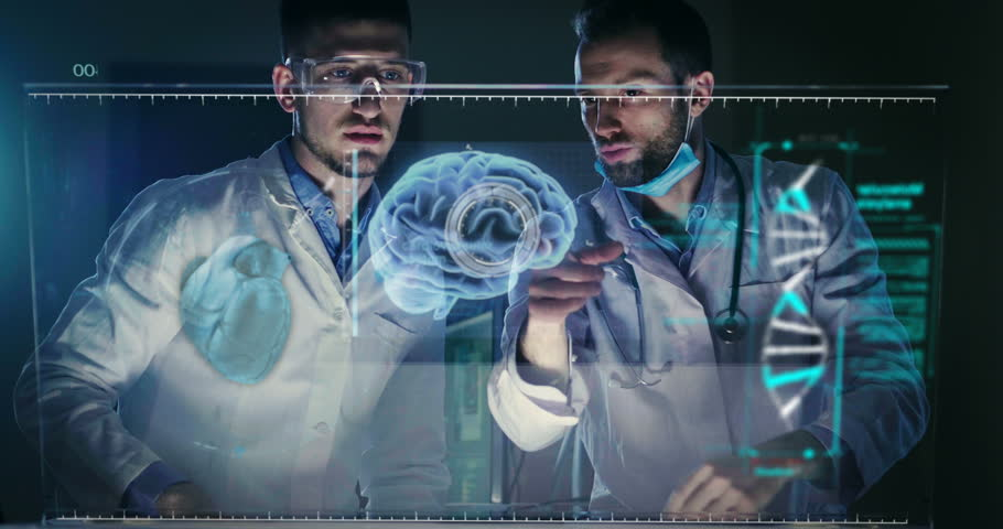 A couple of doctors or scientist analyze the patient's medical situation by checking on a glass monitor with a futuristic holography. Concept of: medicine, doctors, future, holography.