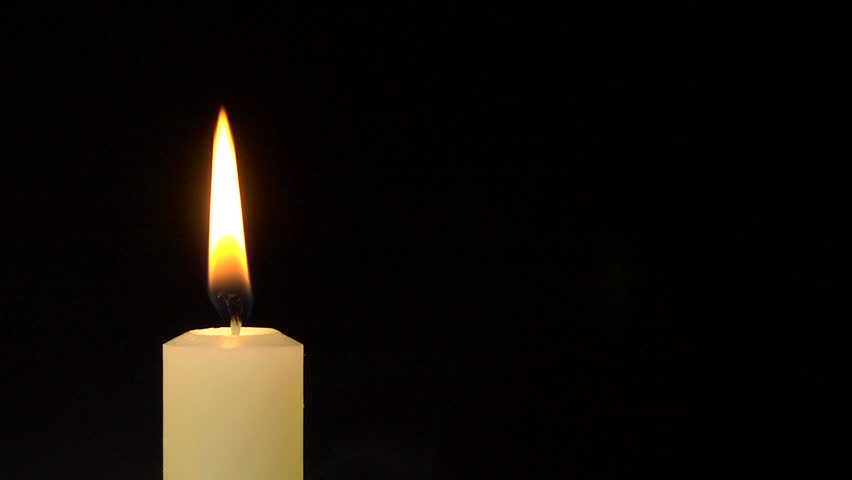 A single white candle burning. Looping for use as a background or illustration of remembrance or celebration. The wind tries to put out the flame, but it recovers each time. The eternal flame.