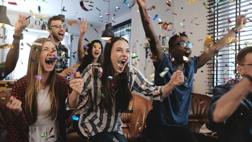Emotion. Multi-ethnic fans celebrate winning. Confetti 4K slow motion. Passionate supporters shout watching game on TV. | Shutterstock HD Video #1009124816