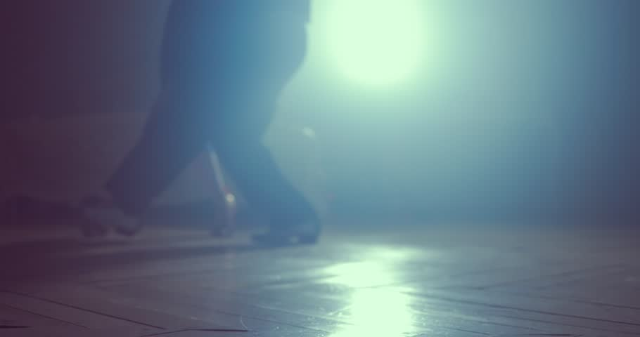 Legs of couple learning to dance tango in the studio. Close up. Silhouette