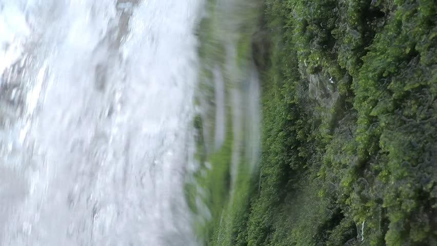 Water river falling from inside a waterfall in slow