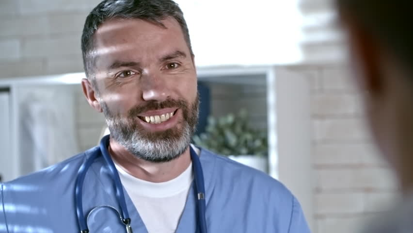 Over the shoulder shot of bearded male doctor in scrubs and stethoscope around his neck smiling and chatting with unrecognizable colleague | Shutterstock HD Video #1009145195