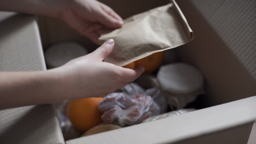 Woman examines products brought by courier. Food delivery services during coronavirus pandemic for working from home and social distancing. Shopping online.