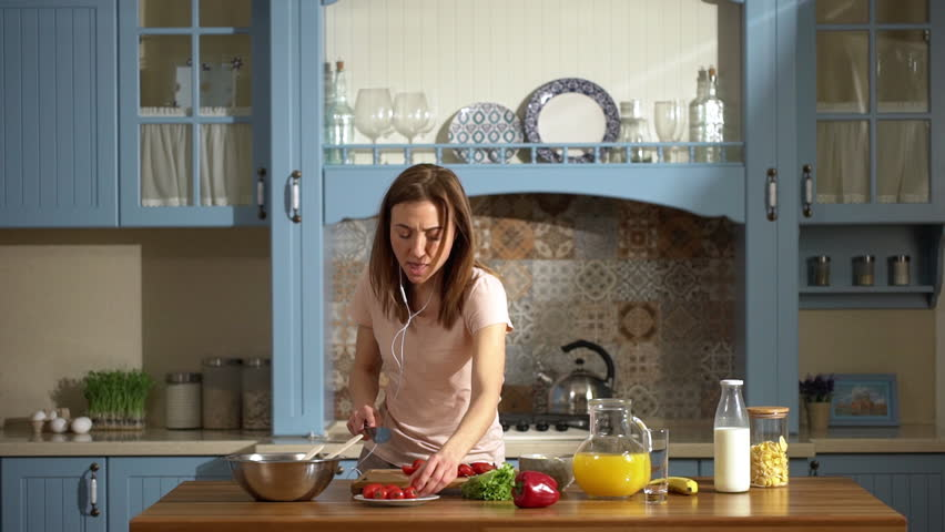 Portrait of joyous energetic woman listening to music via earphones and dancing at home kitchen, while cooking healthy breakfast with fresh vegetables slow motion