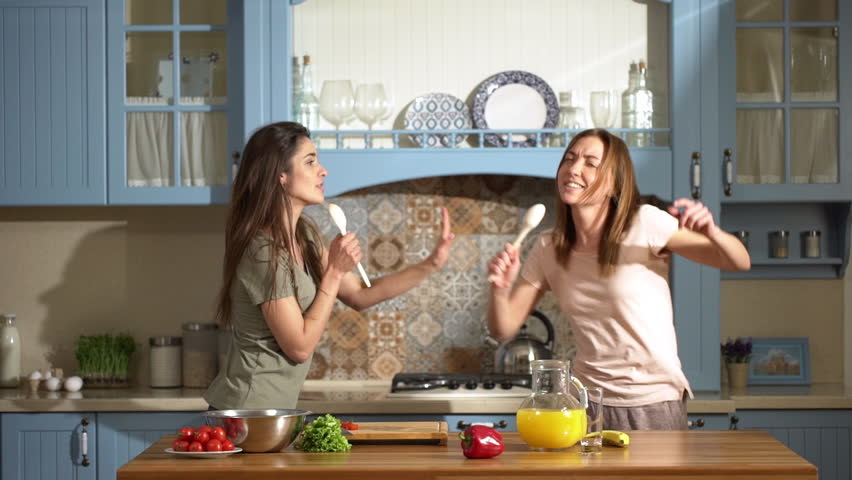 Portrait of two beautiful women dancing and singing at home kitchen using spoons, while cooking healthy breakfast with fresh vegetables and fruits slow motion #1009163000